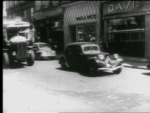B/W 1940s bicycles + traffic on busy city street / people walking on sidewalk in background / Paris, France