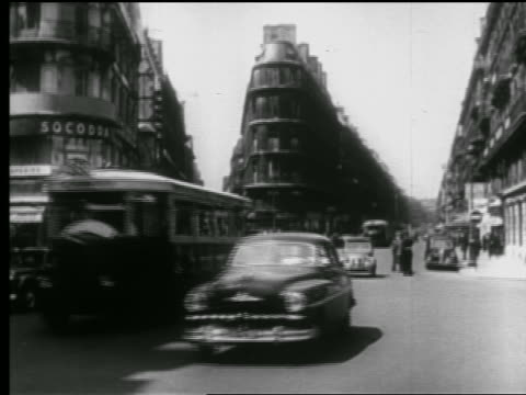 B/W 1940s bicycles, traffic + people crossing busy city street / Paris, France
