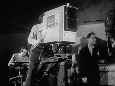 vídeos de stock, filmes e b-roll de 1940s black and white camera operator being pushed on dolly on cbs tv set - câmera de televisão