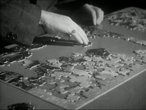 stockvideo's en b-roll-footage met 1940s black and white close up tilt down elderly man putting together jigsaw puzzle / messing it up out of frustration - puzzel