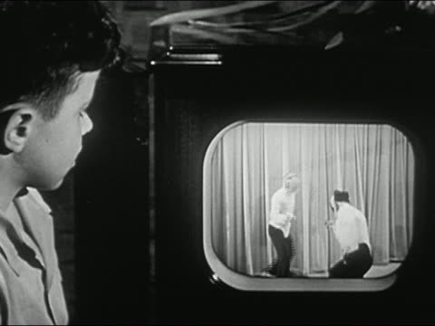 1940s black and white medium shot boy watching fencers on television