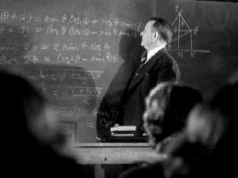 stockvideo's en b-roll-footage met 1940s black and white medium shot calculus professor standing in front of chalkboard covered with equations / students sitting before him / audio - schoolbord