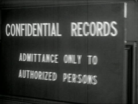 1940s black and white medium shot door to confidential records room opening / young woman jotting down information - filing cabinet stock videos & royalty-free footage