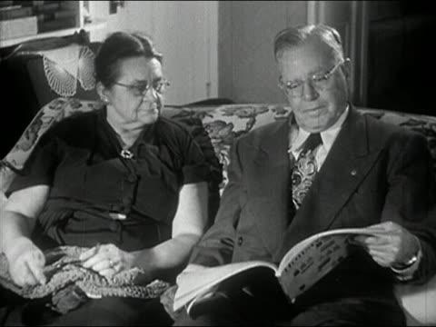 1940s black and white medium shot older couple sitting on sofa / woman putting head on man's shoulder