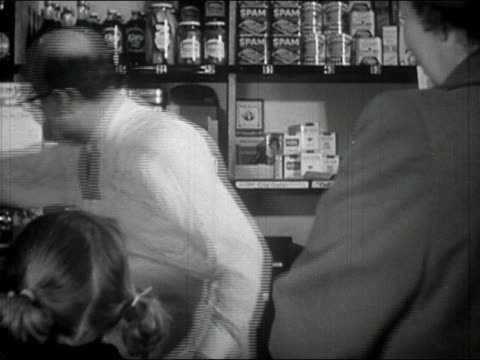 1940s black and white medium shot shopkeeper helping customer at counter - braided hair stock videos & royalty-free footage