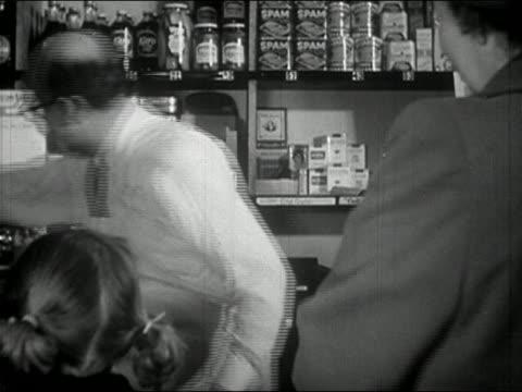 1940s black and white medium shot shopkeeper helping customer at counter