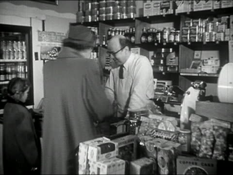 1940s black and white medium shot woman walking away from shopkeeper at store counter / young lingering behind