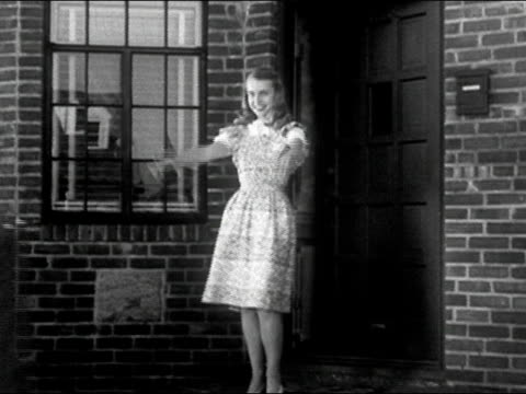 1940s black and white medium shot young woman in apron standing on doorstep / greeting man as he returns from work / couple hugging and kissing / audio - greeting stock videos & royalty-free footage