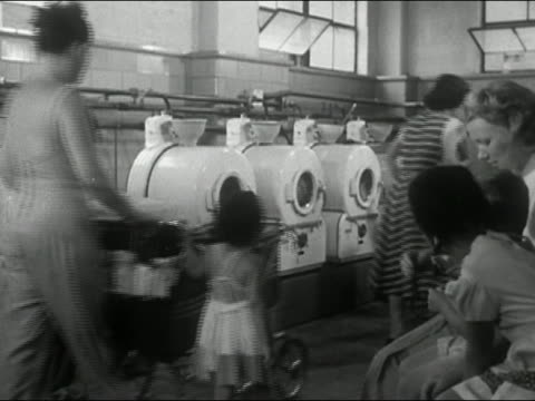 1940s black and white mothers and young children entering laundromat with laundry in baby carriages / New York City