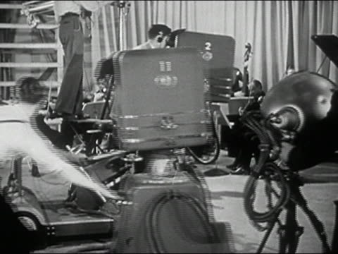 1940s black and white television crew moving cameras and lighting equipment in studio