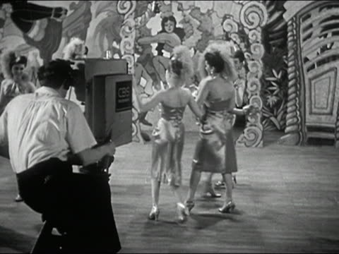 1940s black and white wide shot tv camera operator dollying in to dancers performing on cbs set / pulling back - television camera stock videos and b-roll footage