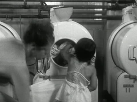 1940s black and white young girl helping mother load laundry into washing machine at laundromat / New York City