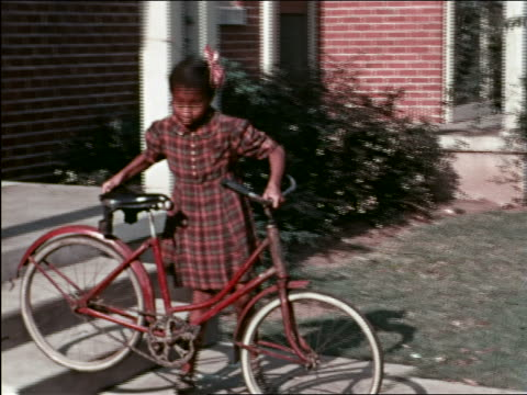 1940s pan black girl pushes bicycle down stairs to sidewalk / man helps her / home movie - handkamera bildbanksvideor och videomaterial från bakom kulisserna