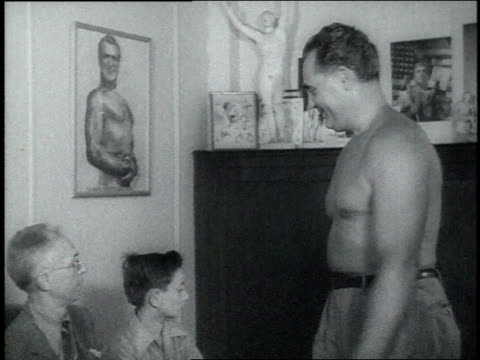 1940s MS bodybuilder Charles Atlas flexing his muscles for a man and a teenage boy