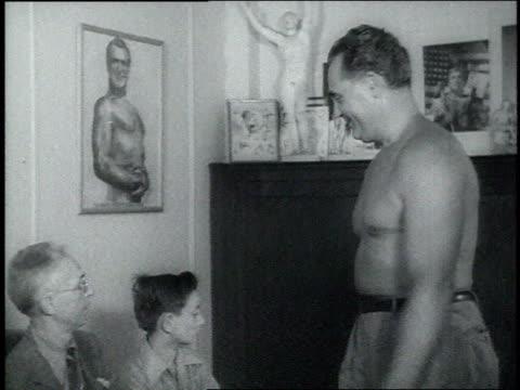 1940s ms bodybuilder charles atlas flexing his muscles for a man and a teenage boy - charles atlas bildbanksvideor och videomaterial från bakom kulisserna