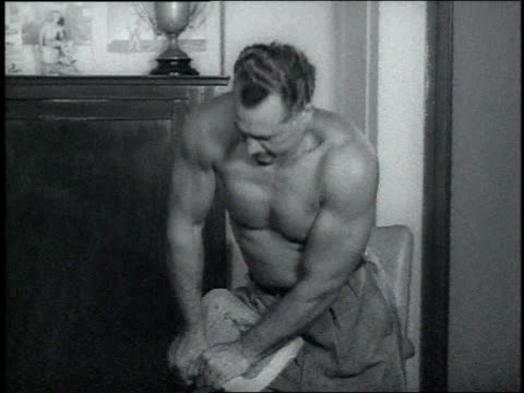 vídeos de stock, filmes e b-roll de 1940s ms bodybuilder charles atlas tries unsuccessfully to tear a telephone book in half - musculação