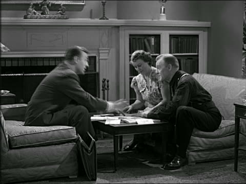 b/w 1940s businessman shows document to middle aged couple in living room / they stand + shake hands - door to door salesperson stock videos & royalty-free footage