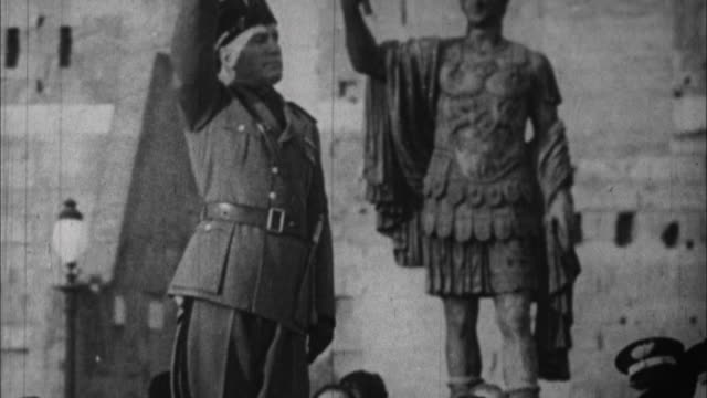1940s b/w ms benito mussolini at soldiers parade emperor augustus statue in background / rome italy - benito mussolini stock videos & royalty-free footage