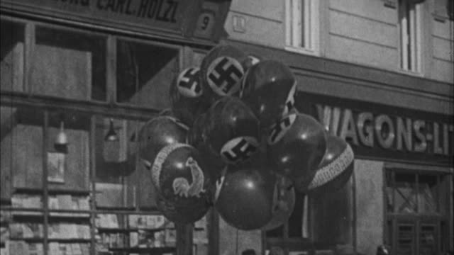 1940s B/W MS PAN Bunch of balloons with swastika being carried on street / Germany