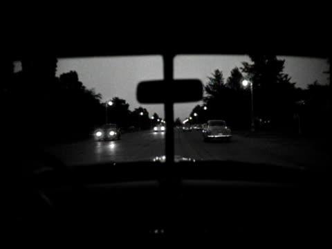 vidéos et rushes de 1940s b/w ws pov driving down city street at dusk / usa - intérieur de véhicule