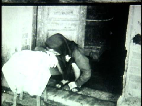 vídeos de stock, filmes e b-roll de 1940s b/w ws eledery woman sitting in depair on doorstep / unknown location - só uma mulher idosa
