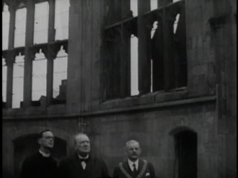 1940s B/W Men including Winston Churchill walking out of a church and into the rubble of bombed streets / United Kingdom