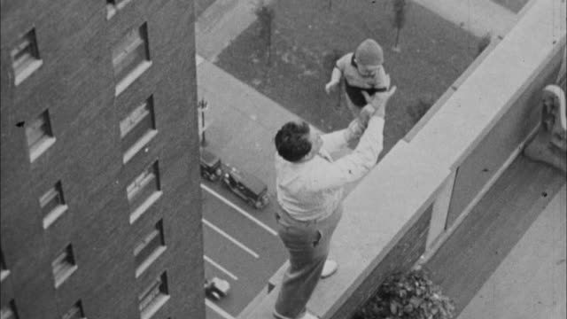 1940s b/w montage man juggles baby on top of building / united states - balance stock videos & royalty-free footage