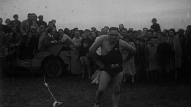1940s b/w montage muscle man holds plane with his teeth / united states - miteinander verbunden stock-videos und b-roll-filmmaterial