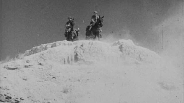 1940s b/w montage soldiers horseback riding on sand dunes / united states - gruppo medio di animali video stock e b–roll