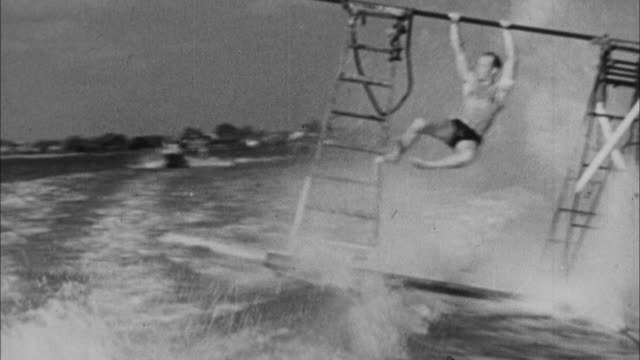 1940s b/w rear muscle man is pulled behind boat on surf board and wipes out / united states - stunt person stock videos & royalty-free footage
