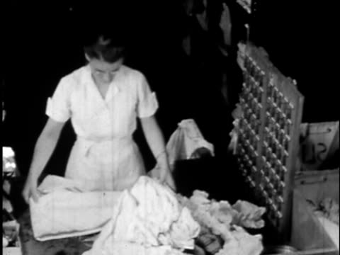 1940s B/W, MS, HA, Woman sorting laundry at commercial cleaners, USA