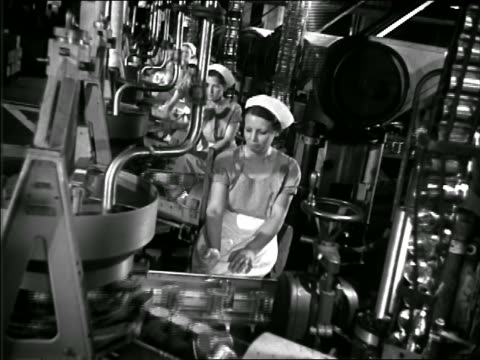 b/w 1940s canted tilt down women working on can assembly line in factory - fließband stock-videos und b-roll-filmmaterial