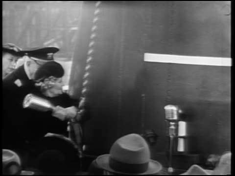 b/w 1940s captain standing next to woman smashing bottle on hull of ship during christening - ship launch stock videos and b-roll footage