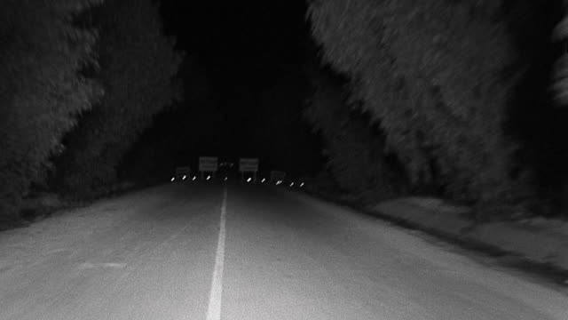 1940s car point of view along highway towards and through detour signs at night