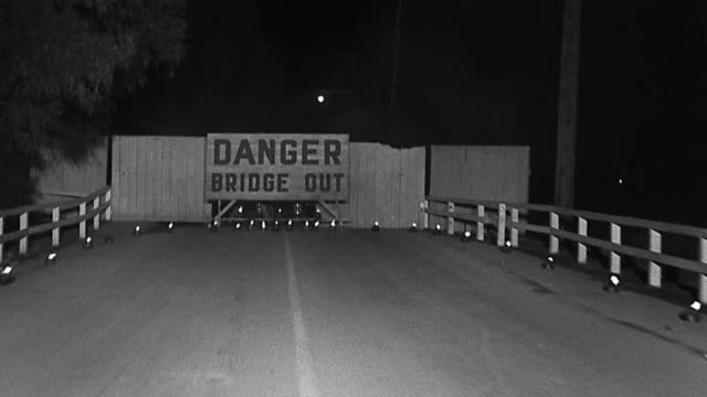 1940s car point of view along highway towards 'danger bridge out' sign / stopping