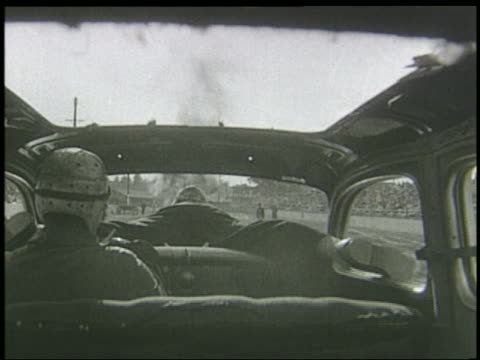 stockvideo's en b-roll-footage met b/w 1940s car point of view from backseat of man strapped onto hood of car / car heading towards wall of fire - passagiersstoel