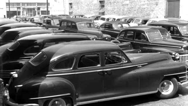 1940s cars crowd a downtown parking lot. - 1940 1949 stock-videos und b-roll-filmmaterial