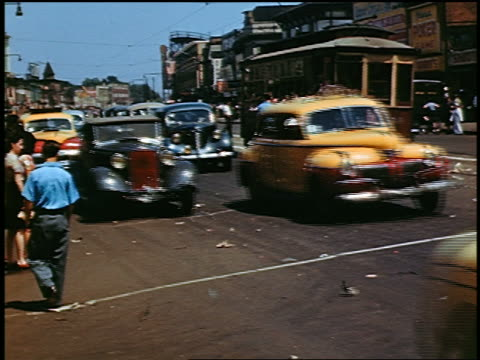 1940s cars on city street past trolleys + pedestrians / coney island, new york - 1940~1949年点の映像素材/bロール