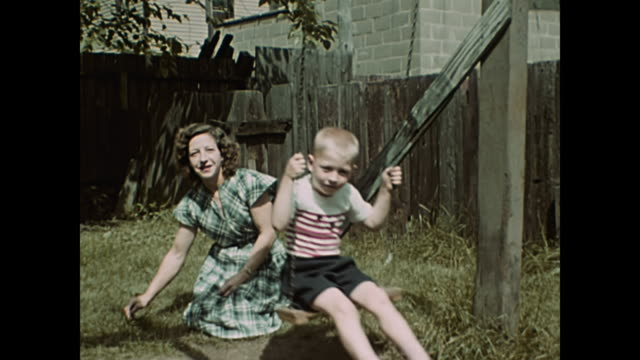 1940s children play swings with parents -  home movie - boys stock videos & royalty-free footage