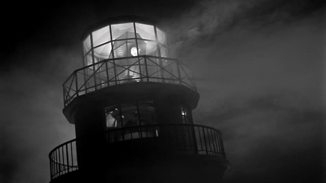 1940s close up canted lighthouse top at night with rotating light - lighthouse stock videos & royalty-free footage