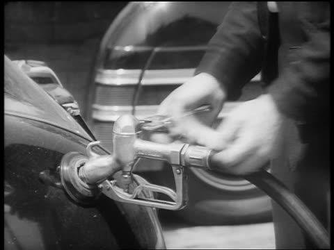 b/w 1940s close up hand of attendant punching gas ration card in gas station / washington dc / newsreel - gas station attendant stock videos and b-roll footage