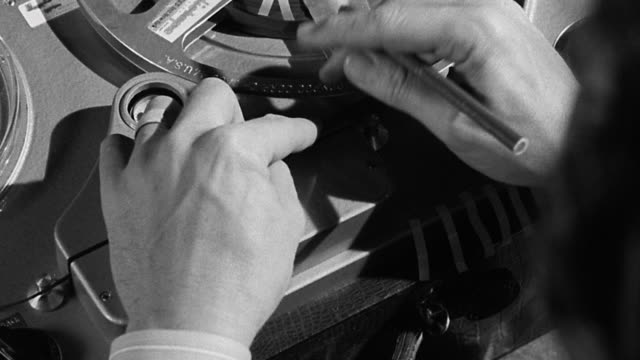 vídeos de stock e filmes b-roll de 1940s close up hands of man editing film on machine, marking with grease pencil and trimming with scissors - editorial