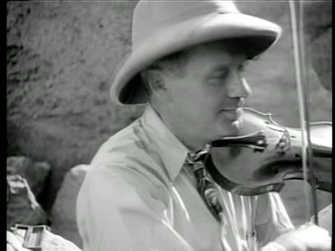 b/w 1940s close up jack benny in pith helmet shaking head while playing violin on uso tour / egypt / doc - solo uomini di età media video stock e b–roll