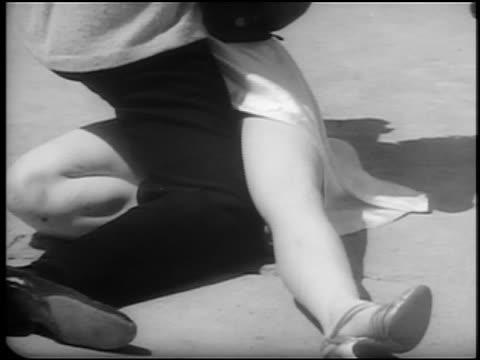 vídeos de stock e filmes b-roll de b/w 1940s close up pan legs of couple with women in splits / others jitterbugging on beach / newsreel - dança jive