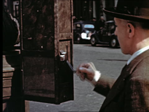 vidéos et rushes de 1940s close up man in hat pushing lever + taking bus ticket from box on sidewalk / paris, france - 60 64 ans