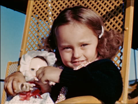stockvideo's en b-roll-footage met 1940s close up portrait small girl cuddling with doll in chair outdoors / travelogue - pop speelgoed