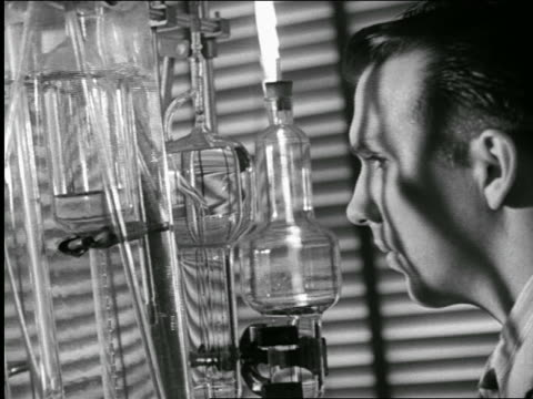 b/w 1940s close up profile scientist looking at bubbling beakers in laboratory / industrial - scientific experiment stock videos & royalty-free footage