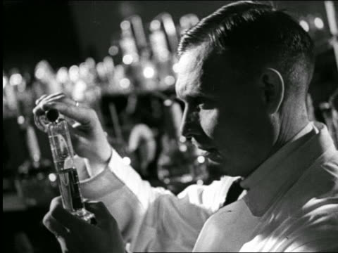 b/w 1940s close up profile scientist looking at test tube in laboratory / industrial - scientific experiment stock videos & royalty-free footage
