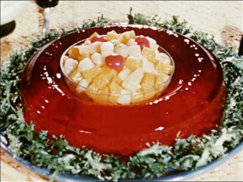 1940s close up red gelatin mold with bowl of fruit salad in center / industrial /audio - gelatin stock videos and b-roll footage