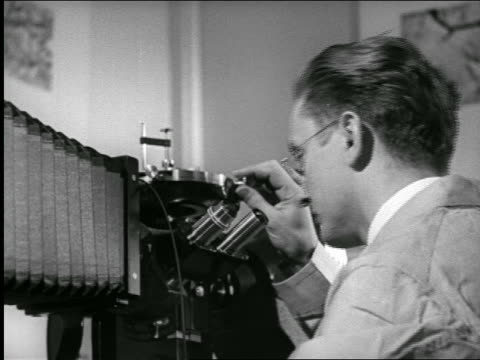 stockvideo's en b-roll-footage met b/w 1940s close up scientist looking into microscope in laboratory / industrial - 1940